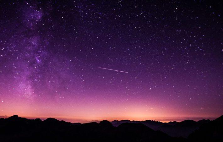 Una stella cadente in un paesaggio notturno